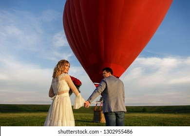 Valentine's Day. A woman with a bouquet of red roses and her boyfriend holding hands and go to red hot air balloon. Marriage proposal, engagement, after which a couple in love flying on a honeymoon