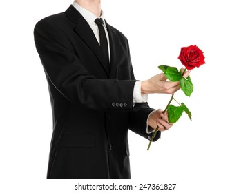 Valentine's Day and Women's Day theme: man's hand in a suit holding a red rose isolated on white background in studio