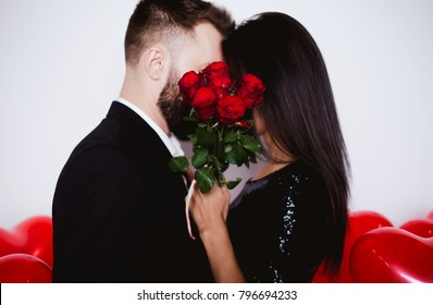 Valentine's Day. Young beautiful couple kisses behind a bouquet of roses. Women's Day