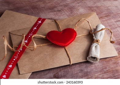 Valentine's day.Envelope with  red hearts on Brown wooden background.