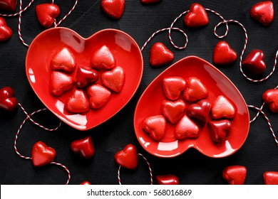 Valentine's dessert, mix of chocolates in the shape of hearts on black background, sweet love background, top view