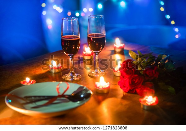 Valentines dinner romantic love concept / Romantic table setting decorated with fork spoon on plate and couple champagne glass roses with candlelight on wooden table dinner night light background