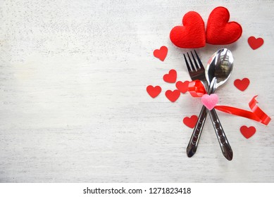 Valentines dinner romantic love food and love cooking concept - Romantic table setting decorated with fork spoon and red heart on white wooden texture background top view copy space