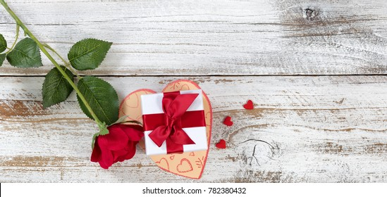 Valentines gift box on top of card with rose and heart shapes in overhead view layout