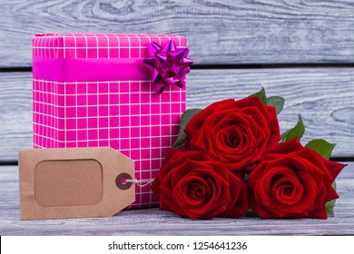 Valentines holiday background. Red roses, gift box and decorative carton tag. Birthday surprise concept.
