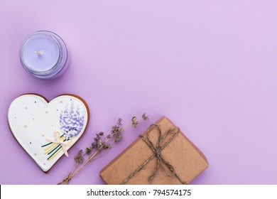 Valentines holiday card with heart biscuit, candle and flowers on purple background