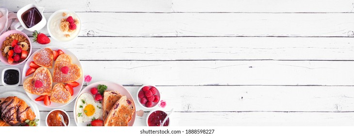 Valentines or Mothers Day brunch corner border. Top down view on a white wood banner background. Heart shaped pancakes, eggs and a variety of love themed food.