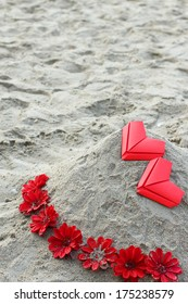 valentine's paper hearts and flower on beach