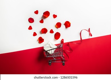 Valentine's shopping concept. Small trolley with a gift and rose petals on a red background