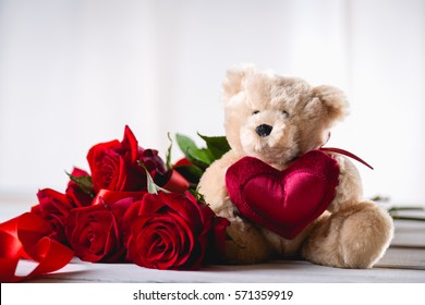 Valentines teddy bear with roses on bright background on wooden table
