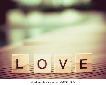 Valentines or Wedding day concept of spelling the word LOVE from 4 wooden blocks. Standing on wooden near swimming pool blurred background.Vintage style and filtered process. Selective focus.