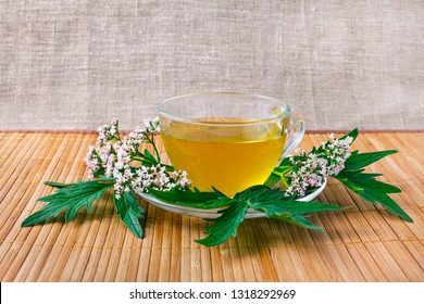 Valerian herb flower sprigs with a cup of calming valerian tea on a bamboo background.