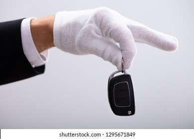 Valet's Hand Holding Car Key Against White Background