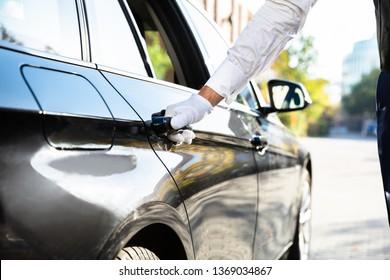 Valet's Hand Opening Black Car Door On Street