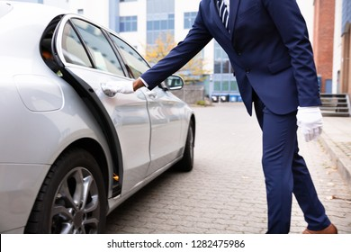 Valet's Hand Opening Grey Car Door On Street