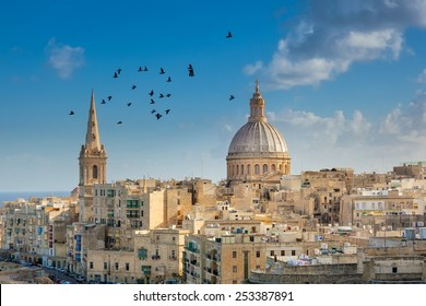 Valetta city buildings with birds flying over them, Malta