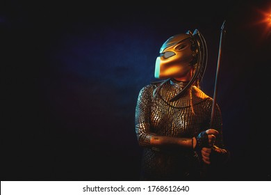 Valkyrie girl looking like an alien in shiny military armor, a strange helmet and a spear in a dark room with plants and vines. Model during a photo shoot, the actress during the shooting of the film