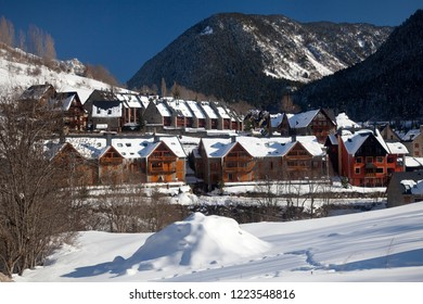 Salardú, Vall d'Aran, Lleida, Catalonia, Spain – February 18, 2012: Panoramic view of of some semi-attached mountain apartments for skiers, covered by snow, on a sunny day