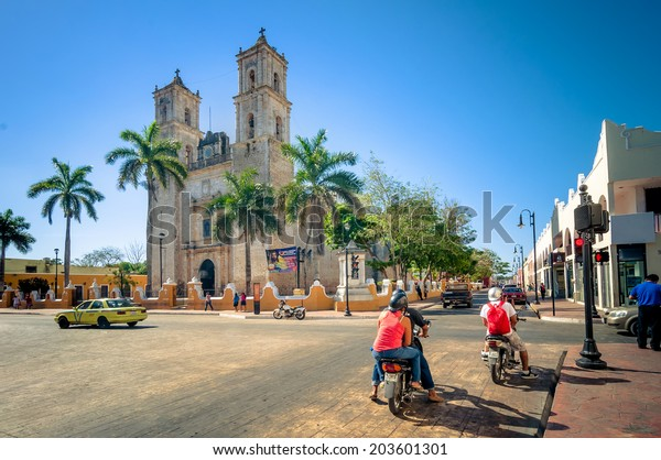 VALLADOLID, MEXICO - APRIL 21, 2014: locals and tourists in main square with Cathedral in Valladolid, Mexico. The city was established in 1543 and named after the capital of Spain, at that time.