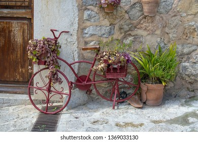 VALLDEMOSSA, MALLORCA, SPAIN - MARCH 21, 2019: Red old bike used as decoration in the old town on March 21, 2019 in Valldemossa, Mallorca, Spain.