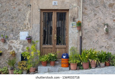 VALLDEMOSSA, MALLORCA, SPAIN - MARCH 21, 2019: Flowers and butane gas bottle outside door in the old town on March 21, 2019 in Valldemossa, Mallorca, Spain.