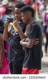 Valle de Chota, Ecuador- March 4, 2019: young men taking photo with phone during the 'Olas del Rio' carnival