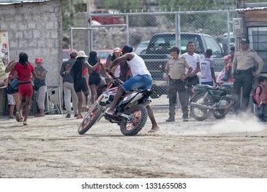 Valle de Chota, Ecuador- March 4, 2019: young man riding his bike on dirt road during 'Olas del Rio' carnaval