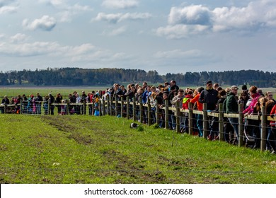 VALLENTUNA, SWEDEN - MAY 2, 2015: Many people waiting outdoors on a large green field by a wooden fence in the country.  Waiting for cows to come out from a barn in Vallentuna Sweden May 2, 2015.