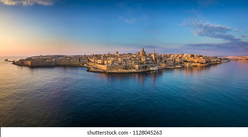 Valletta, Malta - Aerial panoramic skyline of Valletta at sunrise with Our Lady of Mount Carmel church and St.Paul's Anglican Cathedral