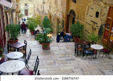 VALLETTA, MALTA - APR 10, 2018 - Tiny cafes with tables on stairs of narrow street,Valletta, Malta