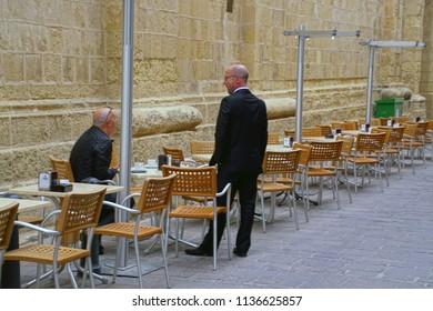 VALLETTA, MALTA - APR 10, 2018 - Men in suits take their morning coffee at outdoor table in Valletta, Malta