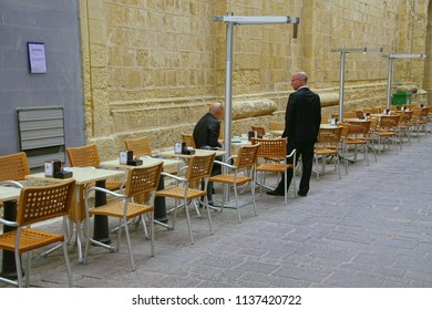 VALLETTA, MALTA - APR 10, 2018 - Men in suits take their morning coffee at outdoor table in Valletta, Malta