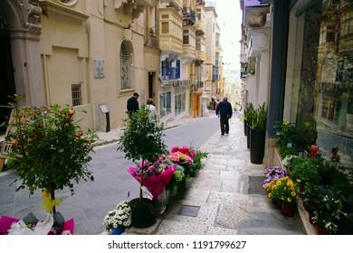 VALLETTA, MALTA - APR 10, 2018 - Walkers on narrow streets of Valletta, Malta