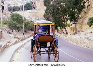 VALLETTA, MALTA - APR 10, 2018 - Horse and carriage descends road in Valletta, Malta