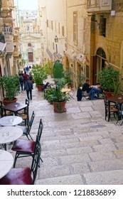 VALLETTA, MALTA - APR 10, 2018 - Tiny cafes with tables on stairs of narrow street,Valletta, Malta