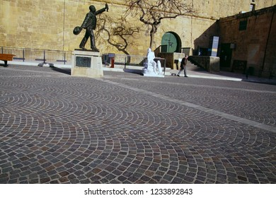 VALLETTA, MALTA - APR 10, 2018 - Statue and twisted tree outside medieval fortifications of Valletta, Malta