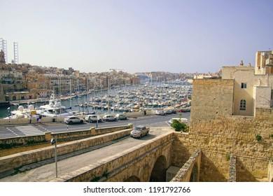 VALLETTA, MALTA - APR 11, 2018 - Waterfront marina with yachts and sailboats, walls of Malta Maritime Museum, Birgu Vittoriosa, Malta