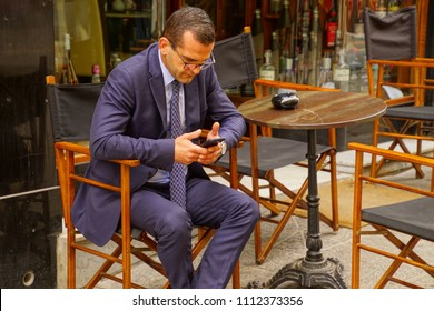 VALLETTA, MALTA - APR 12, 2018 - Business man with cell phone at a coffee shop in Valletta, Malta