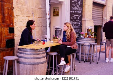 VALLETTA, MALTA - APR 9, 2018 - Young women relax with an afternoon wine on the main street of  Valletta, Malta