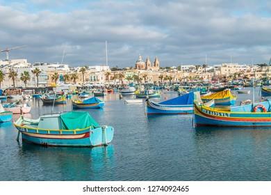 Valletta, Malta - December 23, 2018;Maltese fishing boats in Marsaxlokk at sunrise