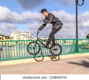 Valletta, Malta - December 4, 2018;Teenager on a BMX bike does a stunt on the city's seafront on a sunny day