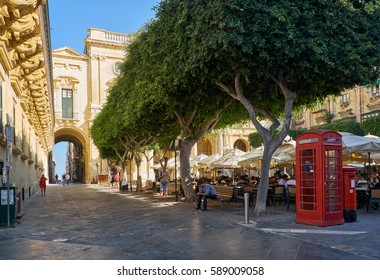VALLETTA, MALTA - JULY 24, 2015: The view of the Old Theatre Street with the outdoor cafe full of people in the summer day and red telephone booth. Valletta, Malta