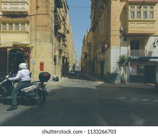 Valletta, Malta - July 4, 2018: Corner of Merchants Street and St Nicholas Street, City Life in Valletta, Capital of Malta, Summer 2018