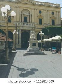 Valletta, Malta - July 4, 2018: Queen Victoria Statue on Republic Square, National Library of Malta in background