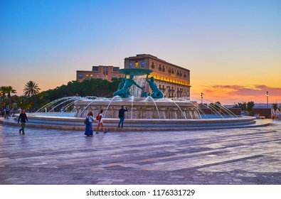 VALLETTA, MALTA - JUNE 17, 2018: Walk the Nelson Avenue with a view on picturesque Triton Fountain in gentle sunset light, on June 17 in Valletta.
