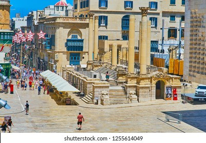 VALLETTA, MALTA - JUNE 18, 2018: People walk at the ruins of Royal Opera House, surrounded by outdoor cafes and tourist stores, on June 18 in Valletta.