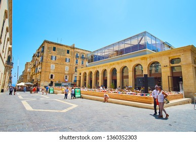 VALLETTA, MALTA - JUNE 19, 2018: The stone building of the Food Market with tall arcades located in Merchants street of old town, on June 19 in Valletta