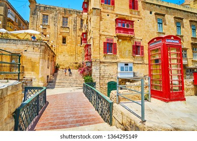 VALLETTA, MALTA - JUNE 19, 2018: The vintage British red telephone box a the tiny bridge, connecting old town and St Barbara Bastion, on June 19 in Valletta.