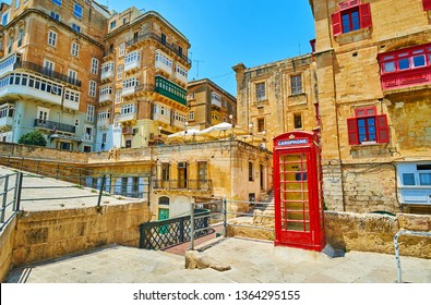 VALLETTA, MALTA - JUNE 19, 2018: The vintage British red phone booth, located on St Barbara Bastion and surrounded by medieval living quarrters of old town, on June 19 in Valletta.