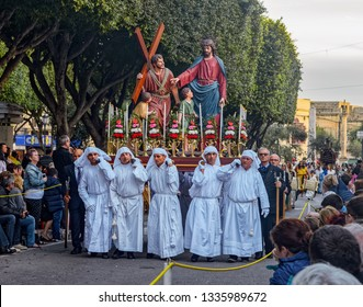 VALLETTA, MALTA - Mar 30, 2018: Men dressed in traditional white robes carry a statue for a Passion of Christ Re-enactment, during a Good Friday procession.